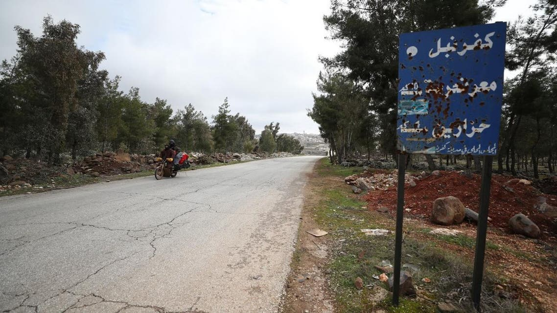 Syrians on a motorcycle leave the deserted city of Kafranbel, south of Idlib city in the eponymous northwestern Syrian province, on February 15, 2020. (AFP)