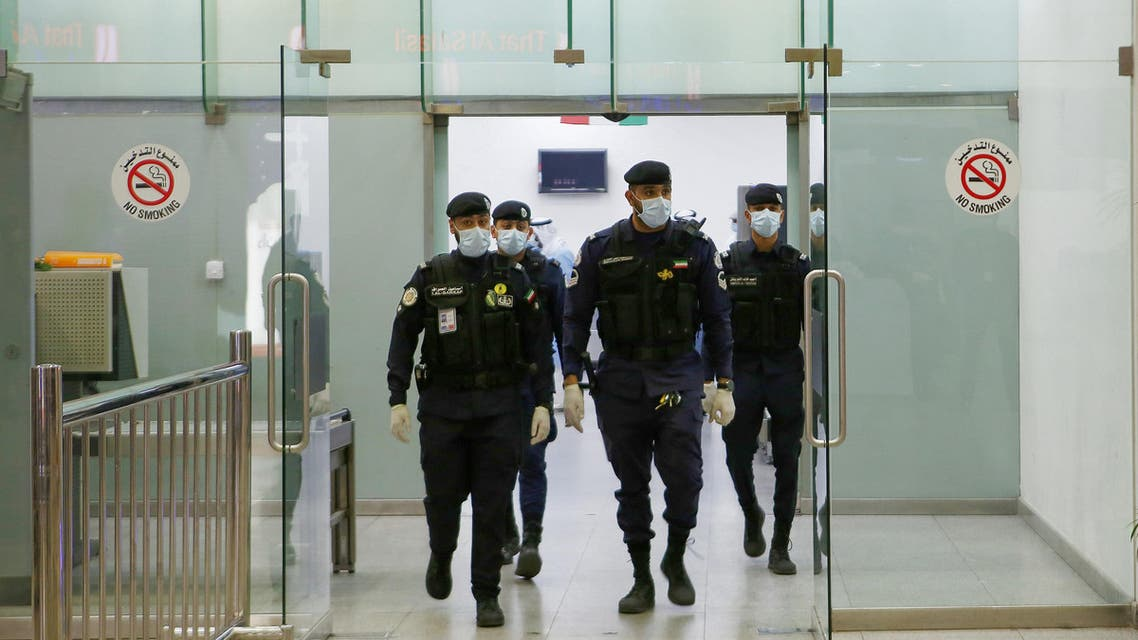 Kuwaiti policemen wearing protective masks wait at Sheikh Saad Airport in Kuwait City, on February 22, 2020, before transferring Kuwaitis arriving from Iran to a hospital to be tested for coronavirus. (AFP)