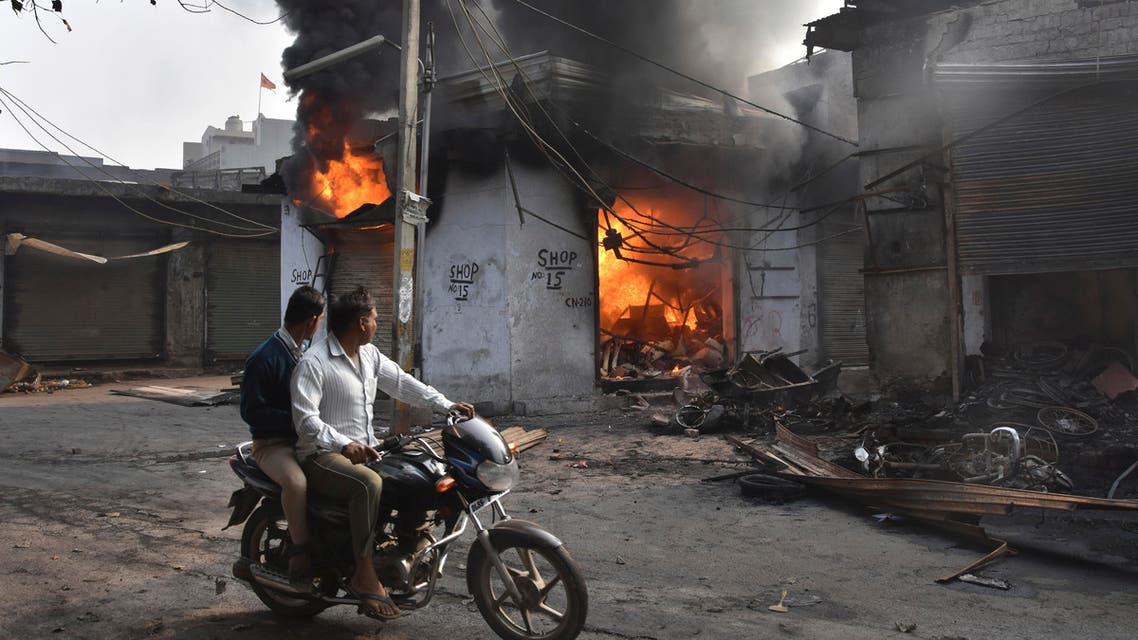 A motorcyclist drives past shops that were set on fire by mobs in New Delhi on Feb. 26, 2020. (Photo: AP)