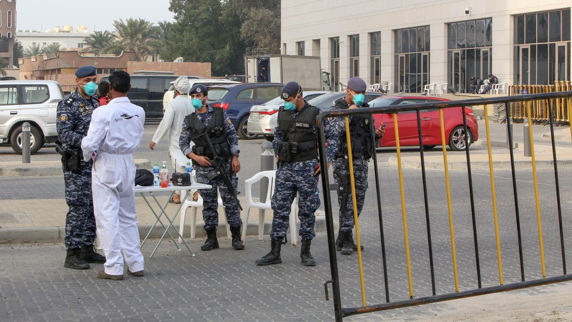 Members of Kuwait's national guard wearing safety masks keep watch outside a hotel in the capital where Kuwaitis returning from Iran are quarantined and tested for coronavirus COVID-19, on February 24, 2020. (AFP)