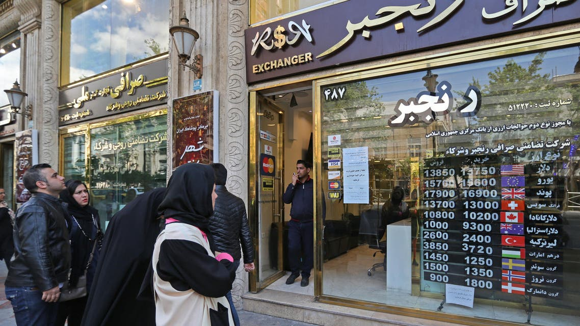 People walk past a currency exchange shop in the Iranian capital Tehran, on April 24, 2019. (AFP)