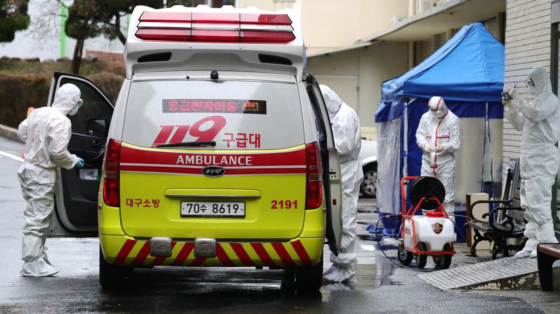A medical worker sprays disinfectant into an ambulance at a hospital where patients infected with the coronavirus are being treated, in the southeastern city of Daegu, South Korea, on February 25, 2020. (AFP)