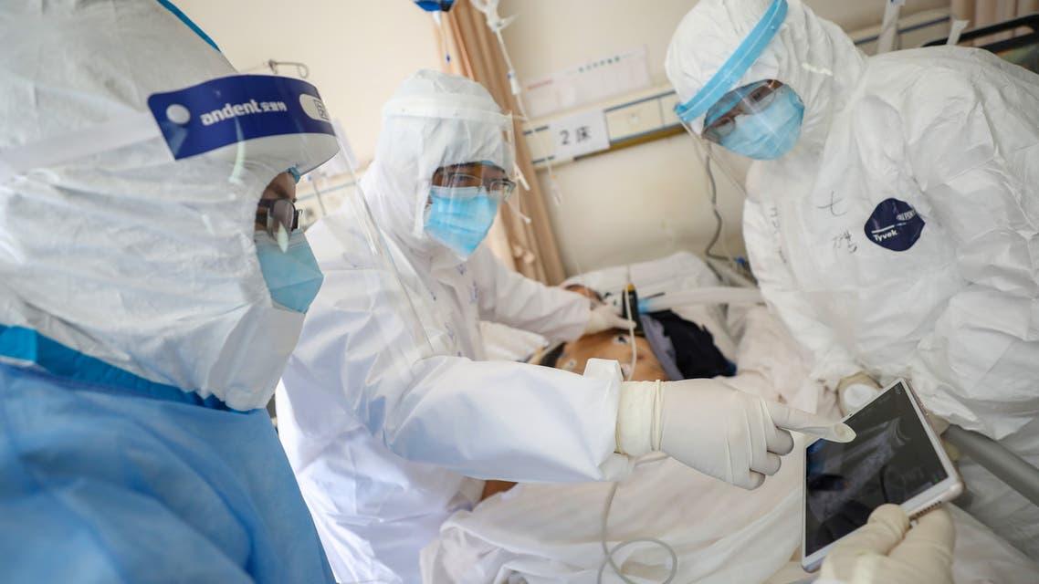عاملون بالمجال الطبي يرتدون بدل وقائية يعالجون مريضا داخل جناح عزل في مستشفى بووهان ( فبراير  2020- رويترز)
