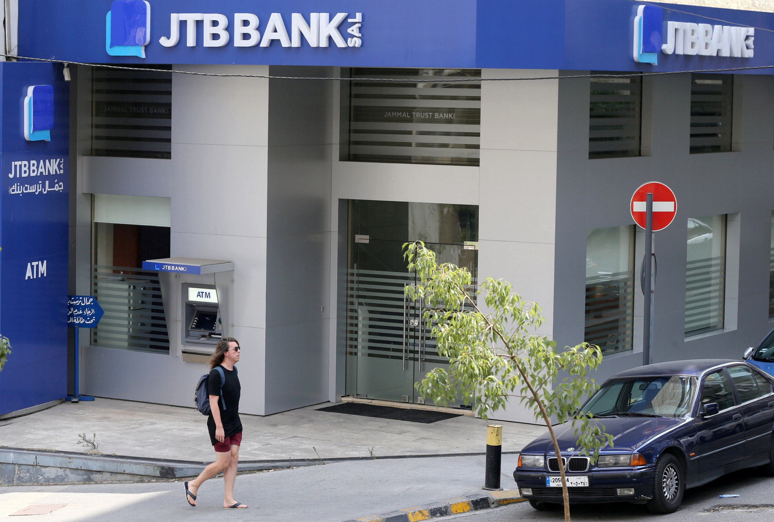 A pedestrian walks past Jammal Trust Bank (JTB) branch in Beirut, Lebanon. (Reuters)