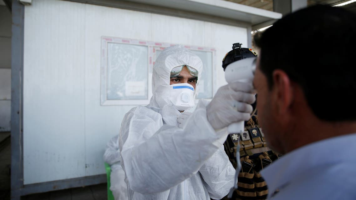عضو في فريق طبي يفحص درجة حرارة مواطن عند نقطة فحص في جنوب الموصل0 رويترز.)