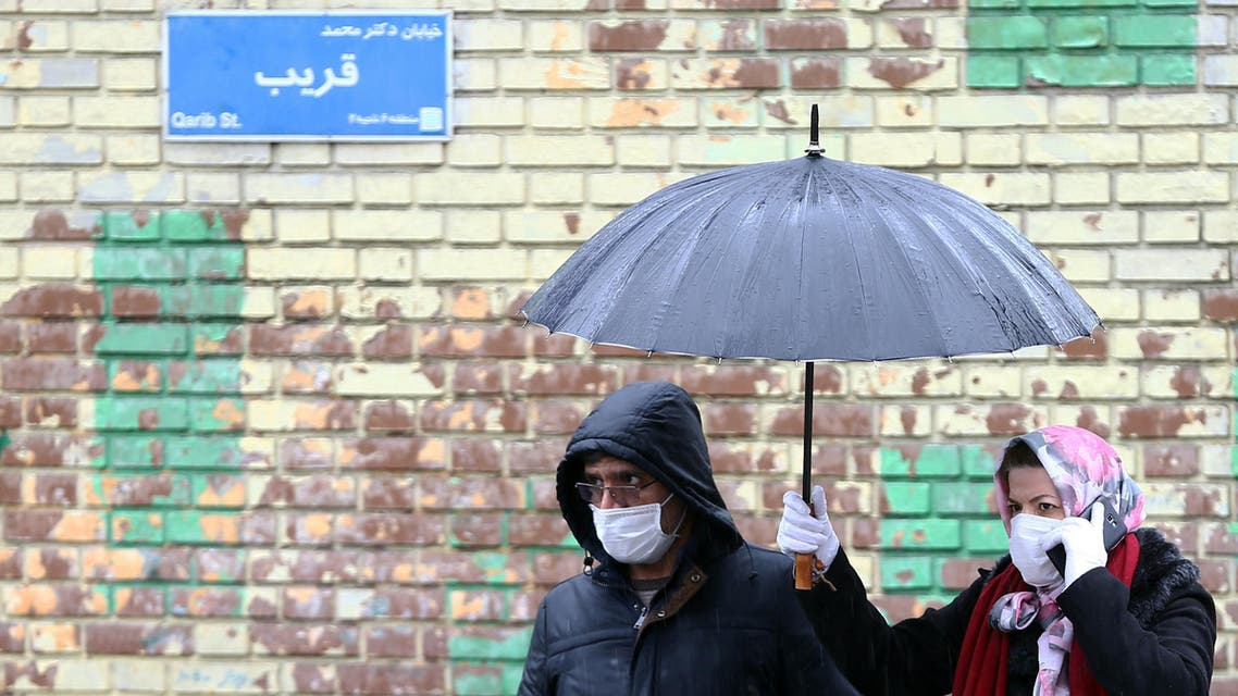 Iranian people wear protective masks to prevent contracting coronavirus, as they walk in the street in Tehran, Iran. (Reteurs)