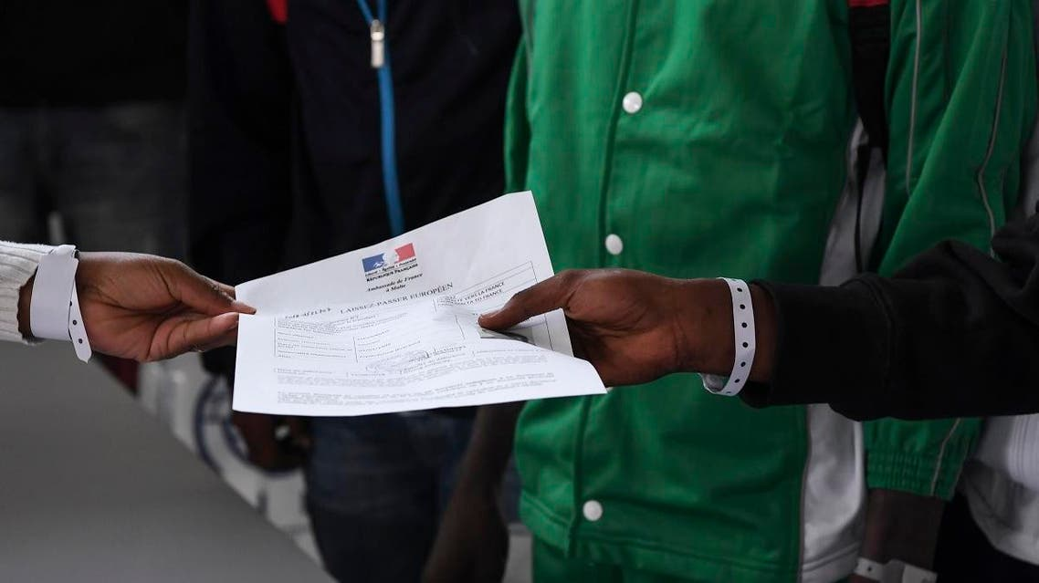 Asylum seekers who have been rescued by the Aquarius rescue ship and another ship in the Mediterranean sea, hold an official document delivered by the French embassy in Malta, as they queue upon their arrival at Roissy-Charles de Gaulle airport, in Roissy-en-France, north of Paris, on August 30, 2018. (AFP)