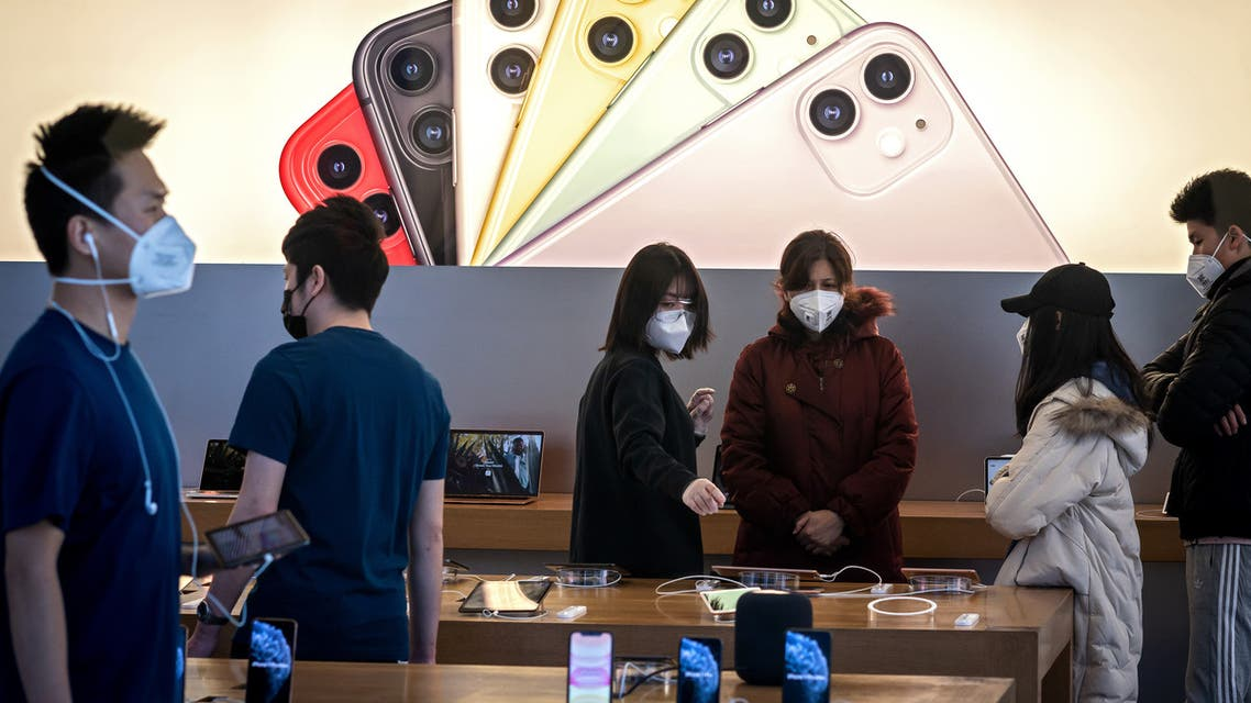 Apple staff and customers, wearing facemasks to protect against the COVID-19 coronavirus, are seen on the shop premises in Beijing on February 22, 2020. The US tech giant said in a statement February 18 its revenue for the current quarter would be below its forecasts, and that worldwide iPhone supply will be temporarily constrained because of the global virus outbreak, notably in China where Apple manufactures most of its devices.