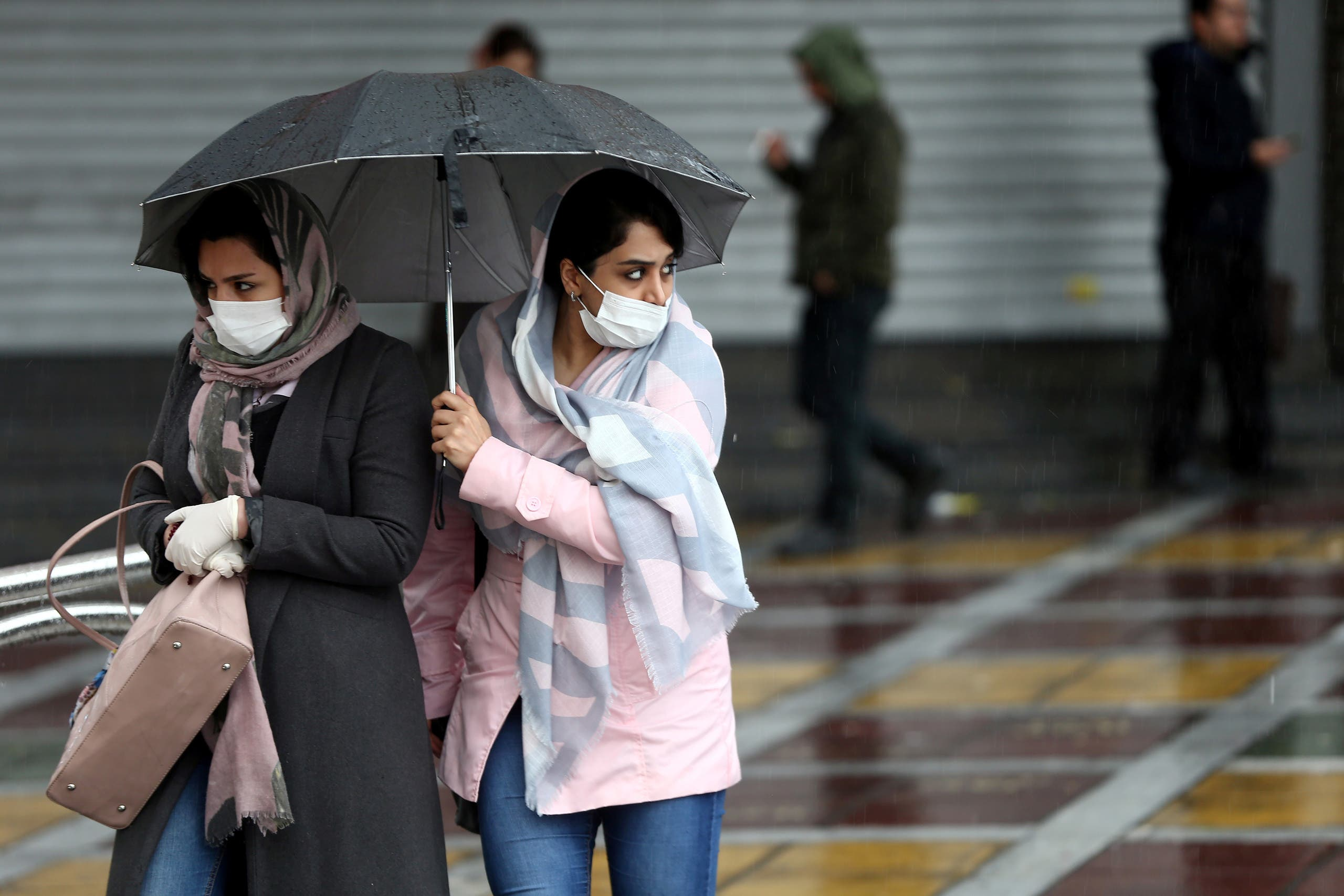 Iranian women wear protective masks to prevent contracting coronavirus, as they walk in the street in Tehran, Iran February 25, 2020. (Reuters)