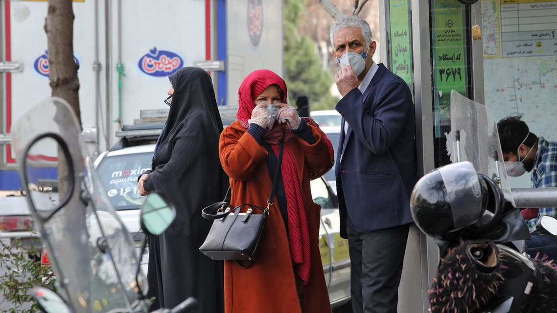 People wearing protective masks wait along the side of a street in the Iranian capital Tehran on February 24, 2020. Iran's government vowed on February 24 to be transparent after being accused of covering up the deadliest coronavirus COVID-19 outbreak outside China as it dismissed claims the toll could be as high as 50. The authorities in the Islamic republic have come under mounting public pressure since it took days for them to admit to accidentally shooting down a Ukrainian airliner last month, killing 176 people. Iran has been scrambling to contain the outbreak since it announced the first two deaths in the holy city of Qom on February 19.