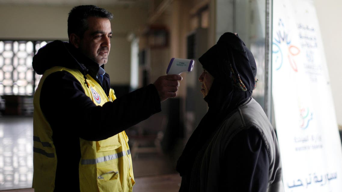 A border official checks the temperature of a passenger as a precautionary measure, following the outbreak of the coronavirus in China, at a border crossing between Syria and Lebanon in Jdaydet Yabous. (Reuters)
