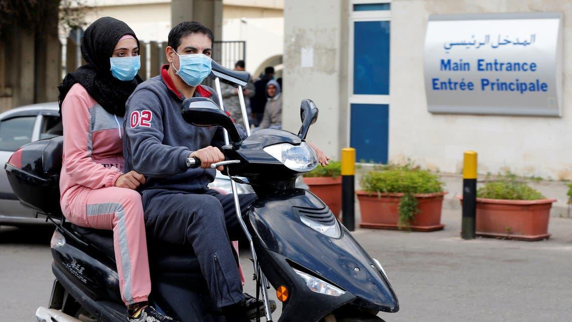 People wearing face masks ride on a motorbike outside Rafik Hariri hospital, where Lebanon's first coronavirus case is being quarantined, in Beirut. (AP)