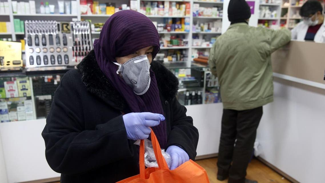 An Iranian woman wears a protective mask to prevent contracting coronavirus, as she is seen at a drug store in Tehran. (Reuters)