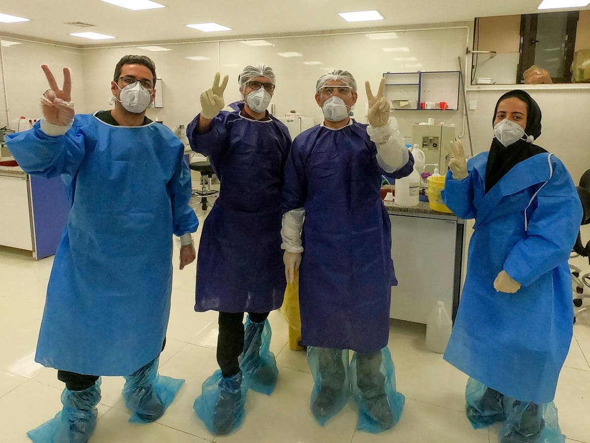 Medics flash the victory sign in a ward dedicated for people infected with the coronavirus, at Forqani Hospital in Qom, 78 miles (125 kilometers) south of the capital Tehran, Iran, Wednesday, Feb. 26, 2020. (AP)