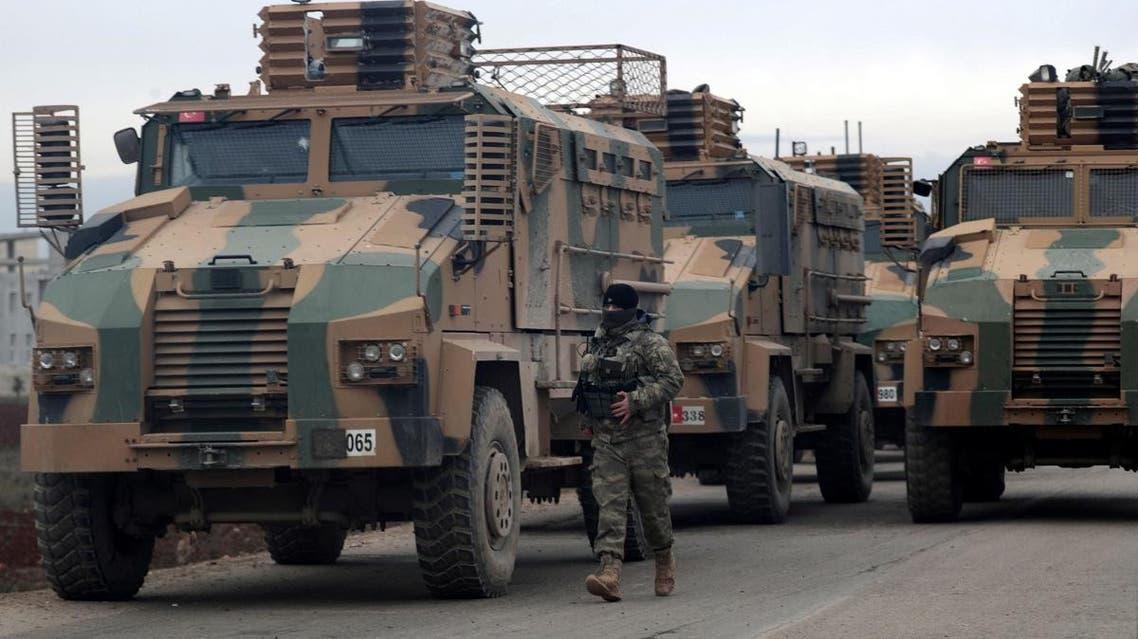 A Turkish soldier walks near Turkish military vehicles in Hazano near Idlib. (Reuters)