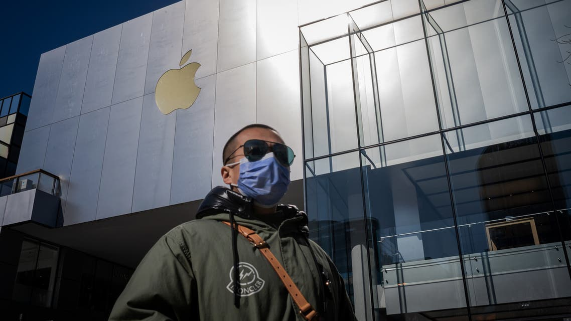 A man wearing a facemask to protect against the COVID-19 coronavirus walks outside an Apple Store in Beijing on February 22, 2020. The US tech giant said in a statement February 18 its revenue for the current quarter would be below its forecasts, and that worldwide iPhone supply will be temporarily constrained because of the global virus outbreak, notably in China where Apple manufactures most of its devices.
