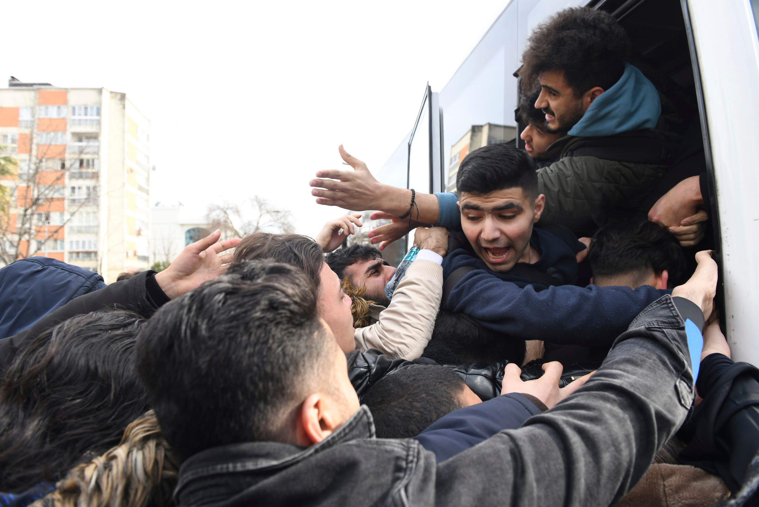 Migrants struggle to board a bus to go to the Greek border, in Istanbul on Feb. 28, 2020. (AP)