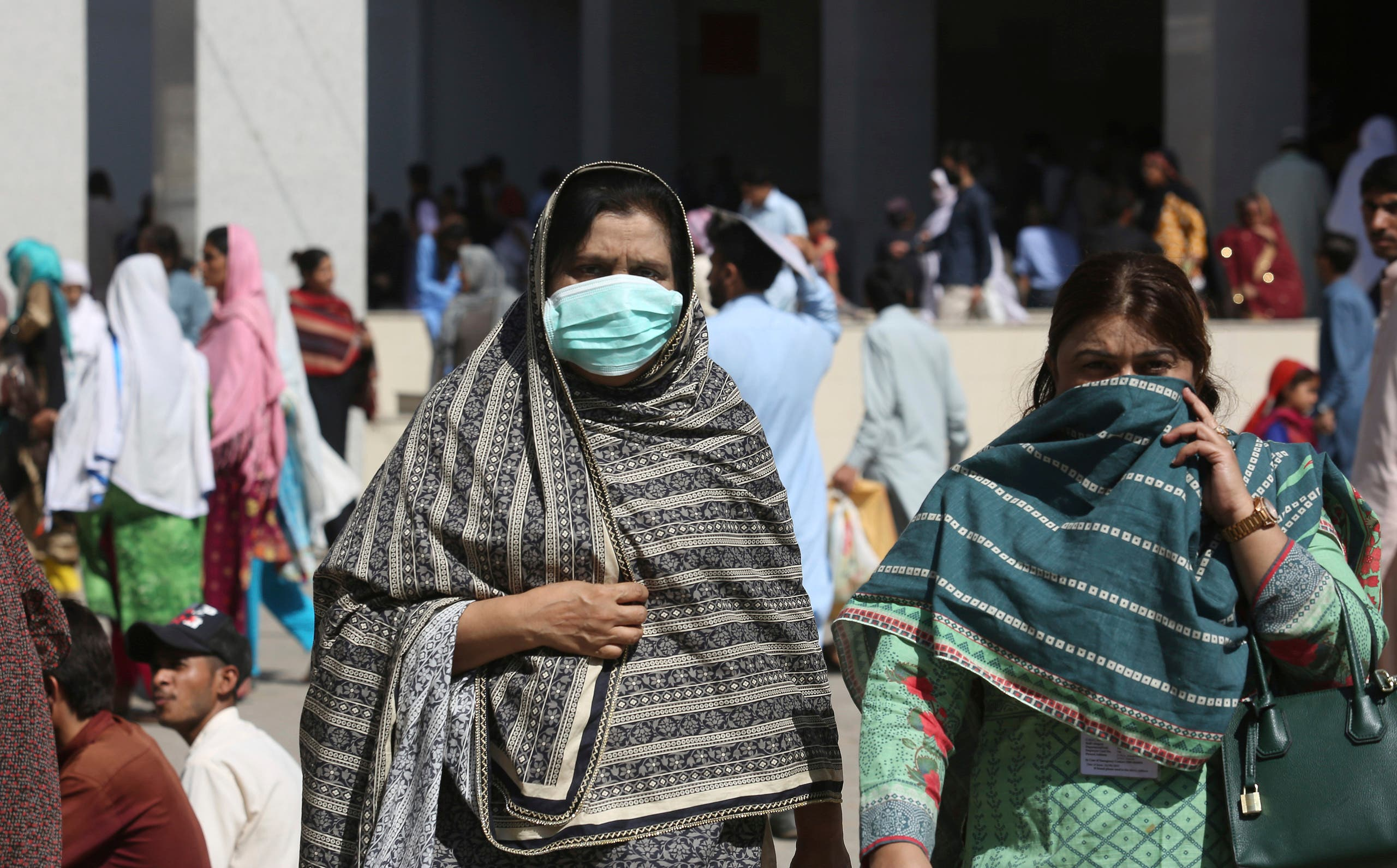 Pakistani women wearing face masks leave the Aga Khan hospital where a patient suspected of having contracted coronavirus was admitted, in Karachi. (AP)