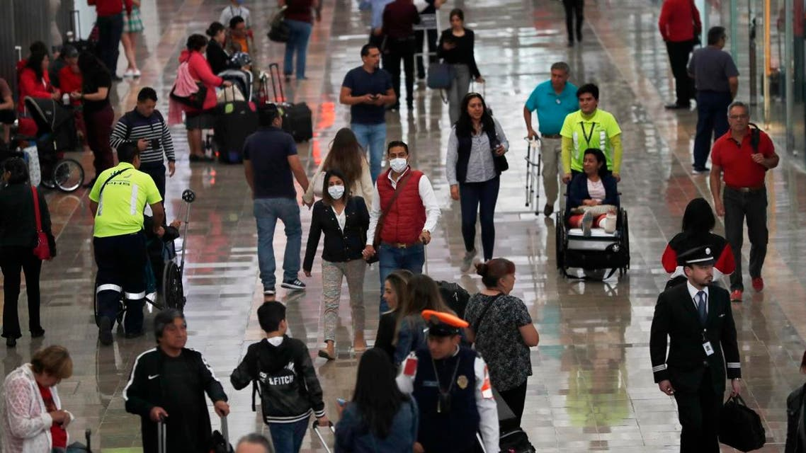 A couple wears protective masks as a precaution against the spread of the new coronavirus at the airport in Mexico City, Friday, February 28, 2020. (AP)