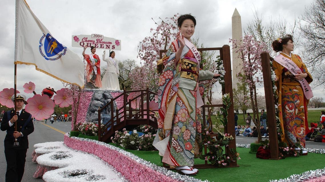 The 2004 Cherry Blossom Queens from Japan wave as they pass the Washington Monument in Washington, Saturday, April 3, 2004. (AP)