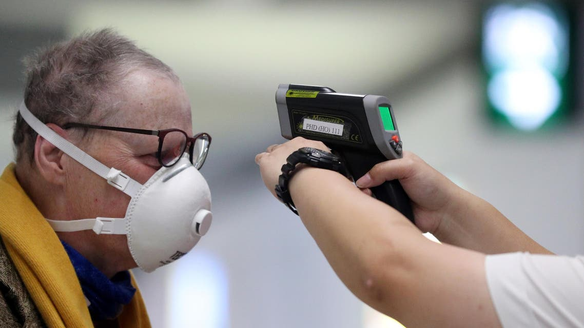 A passenger arriving into Hong Kong International Airport gets his temperature checked by a worker using an infrared thermometer, following the coronavirus outbreak in Hong Kong. (Reuters)