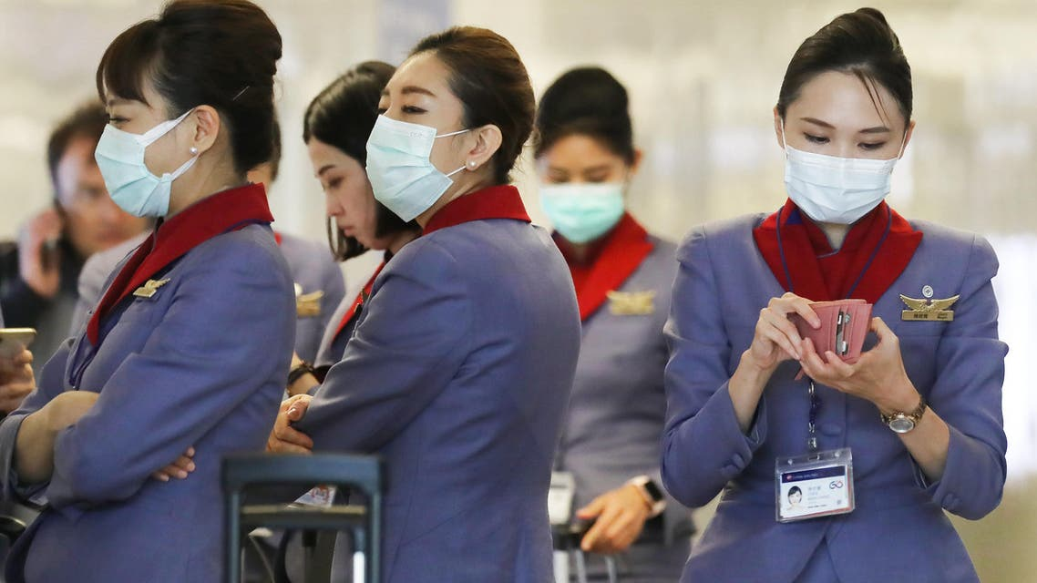 A flight crew from China Airlines, wearing protective masks, stand in the international terminal after arriving on a flight from Taipei at Los Angeles International Airport (LAX) on February 28, 2020 in Los Angeles, California. (AFP)