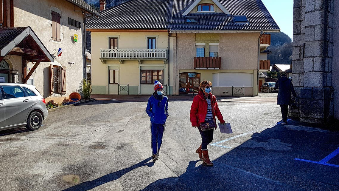 People wear protective face masks as a safety measure against COVID-19, the novel coronavirus, on February 28, 2020, in La Balme-de-Sillingy, central-eastern France, where two new coronarivus cases where detected, adding to the four already found the town. (AFP)