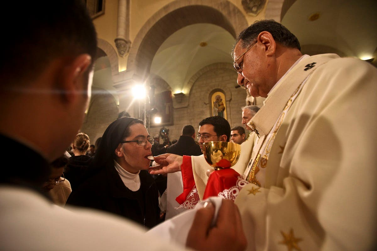 A nun takes communion from Latin Patriarch of Jerusalem Fuad Twal (R) during the midnight mass ceremony which marks the beginning of Christmas Day at the Church of the Nativity in the West Bank town of Bethlehem on December 25, 2010. (AFP)