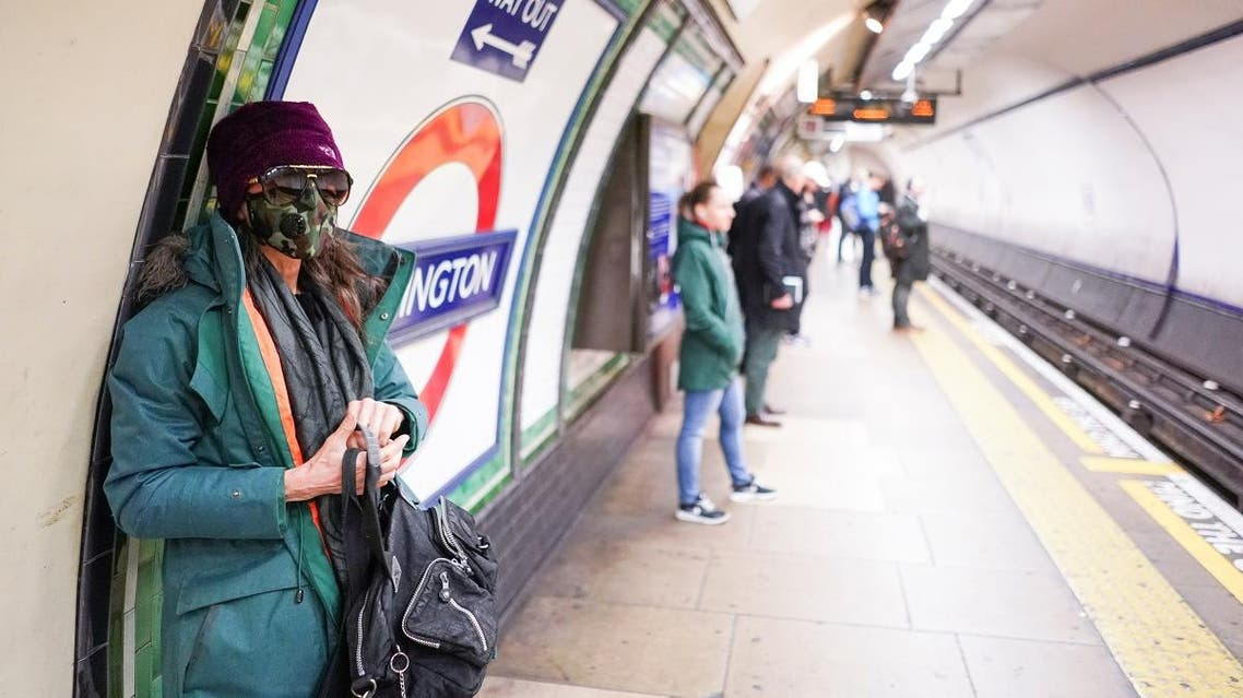 A woman wearing a protective face mask stands on a London Underground platform in central London. (Reuters)