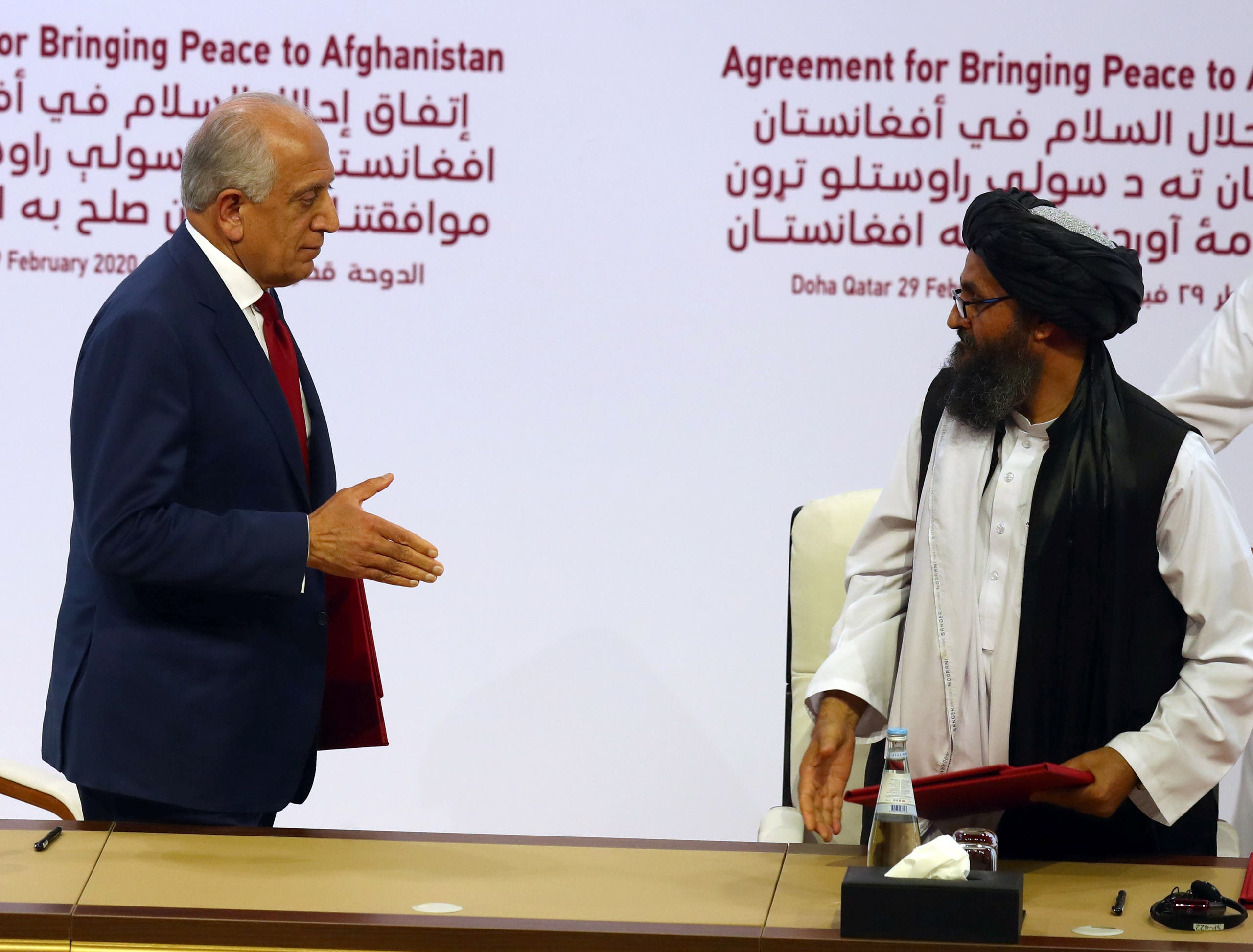 Mullah Abdul Ghani Baradar, the leader of the Taliban delegation, left, and Zalmay Khalilzad, US envoy for peace in Afghanistan, are seen after signing an agreement in Doha, Qatar on February 29, 2020. (Reuters)