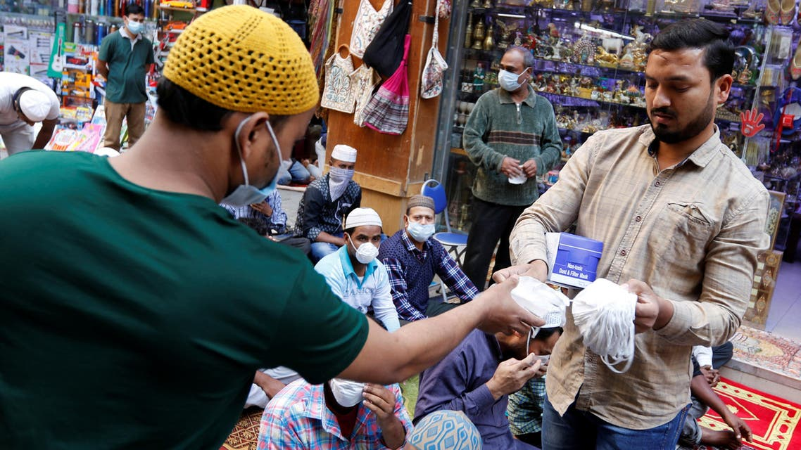 A vendor distributes protective face masks following the coronavirus outbreak, as people pray on a street during Friday prayers in local souq, in Manama, Bahrain, February 28, 2020. (Reuters)