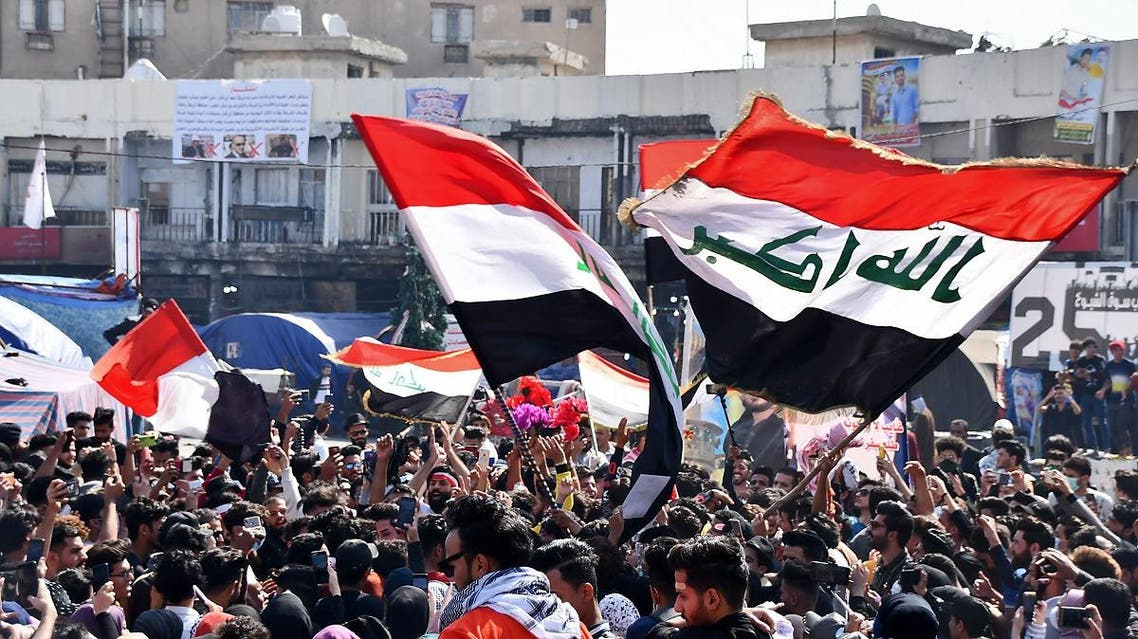 Student protesters, some wearing protective face masks, march with Iraqi national flags during an anti-government demonstration in Iraq's southern city of Nasiriyah in Dhi Qar province on March 1, 2020. (AFP)