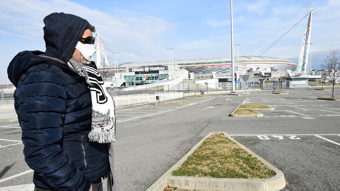 A man wearing a face mask is seen outside the Allianz Stadium, after five Serie A matches were postponed because of the ongoing coronavirus crisis, in Turin, Italy, February 29, 2020. (Reuters)