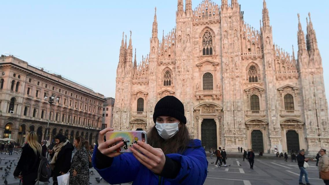 A woman wearing a protective facemask takes a selfie picture in the Piazza del Duomo in central Milan, on February 24, 2020. (AFP)