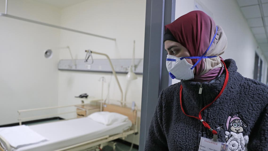 A Lebanese employee wearing a protective mask looks at a bed in a ward where the first case of coronavirus in the country is being treated, at the Rafik Hariri University Hospital on February 22, 2020. (AFP)