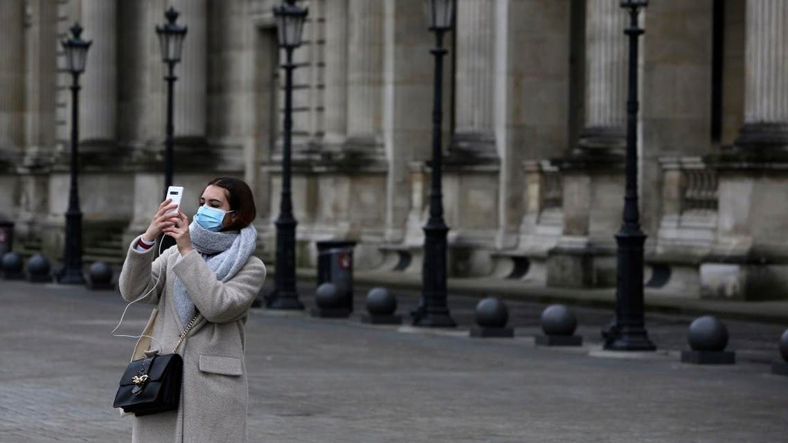 A tourist wearing a mask makes a selfie outside the Louvre museum Friday, February 28, 2020 in Paris. (AP)