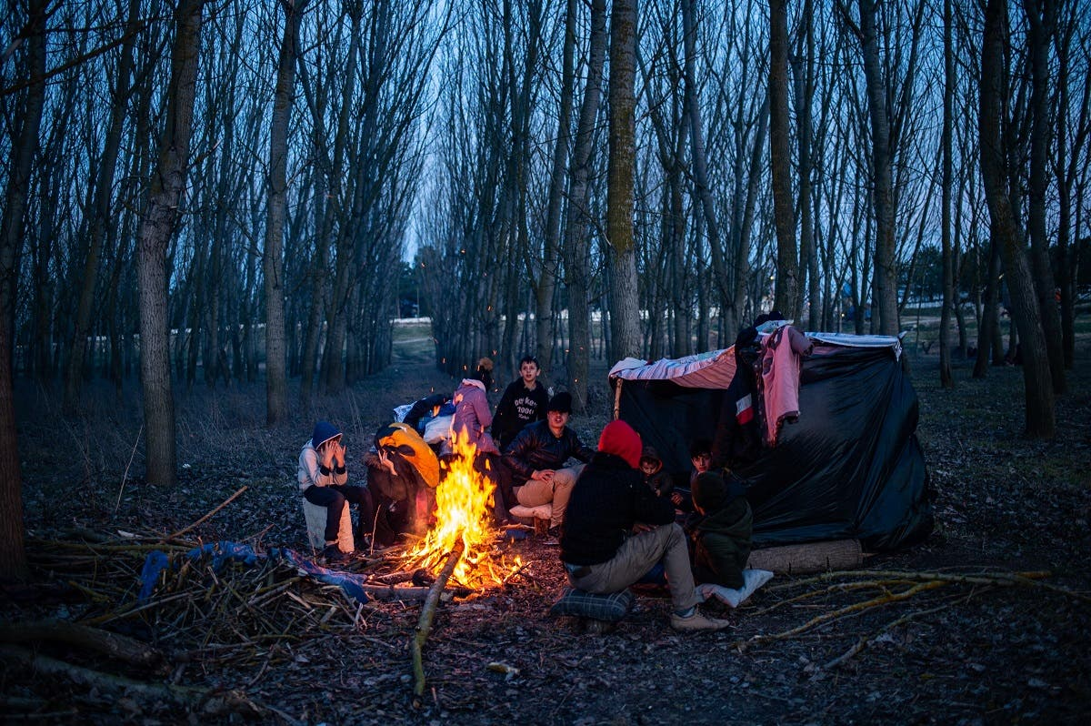A group of migrants rest at a fire as they wait to cross the Maritsa river to reach Greece at the Turkish-Greek border, in Edirne, in northwestern Turkey, on March 1, 2020. (AFP)
