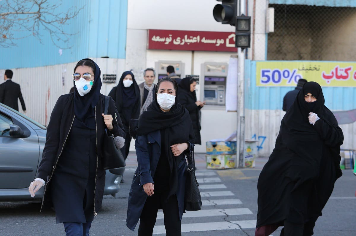 Women wearing protective masks cross a street in the Iranian capital Tehran on March 2, 2020, following the coronavirus outbreak. (AFP)