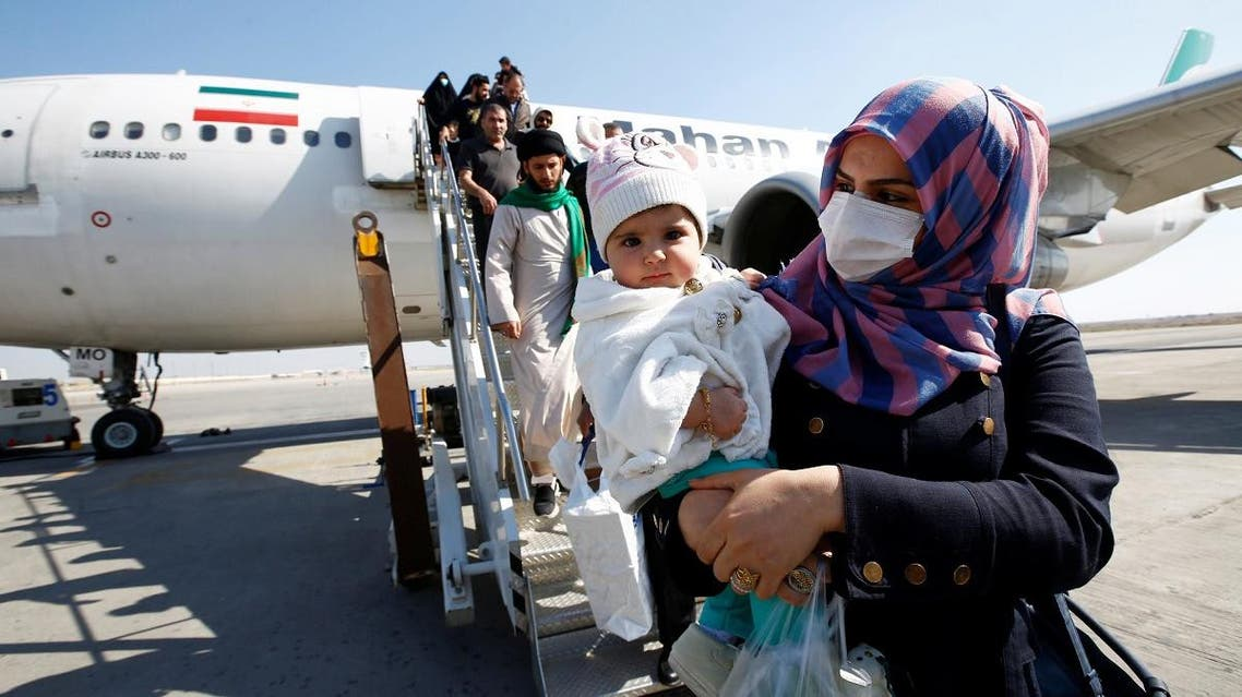 Passengers wearing protective masks disembark from a plane upon their arrival at Najaf airport. (Reuters)