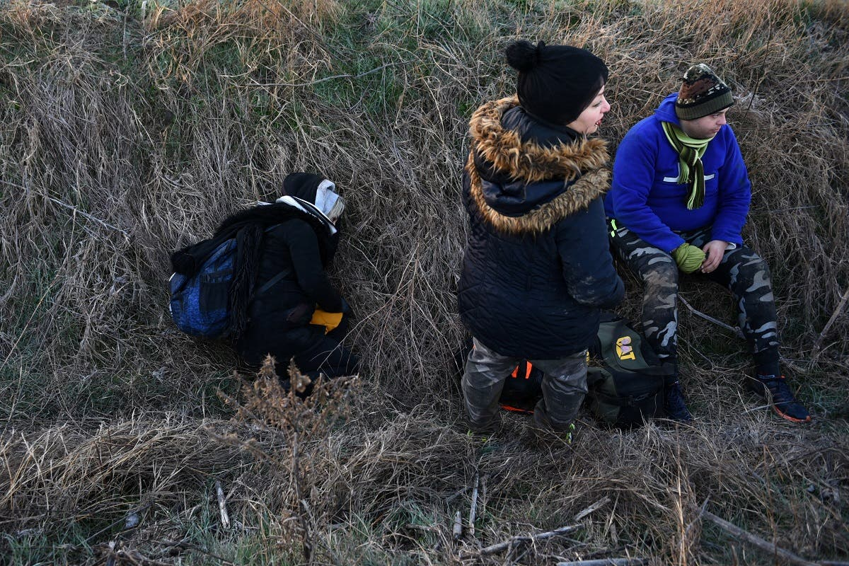 Migrants rest in a ditch, after crossing from Turkey to Greece, near the border crossing of Kastanies. (Reuters)