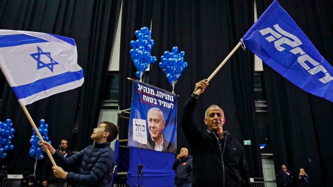 A man waves a Likud party flag while another youth waves an Israeli flag, at the Likud's electoral headquarters in the coastal city of Tel Aviv on March 2, 2020, after polls officially closed. (AFP)