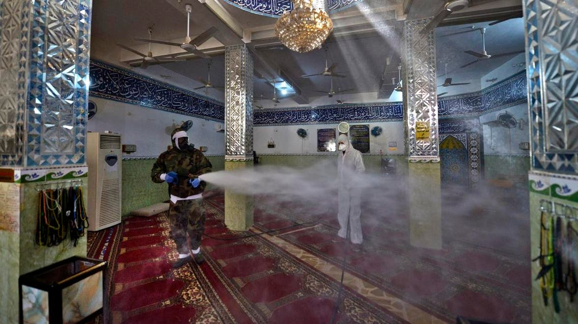 Members of the Iraqi civil defence disinfect a mosque where a recent confirmed case of novel coronavirus infection prays, in the central shrine city of Najaf, on February 3, 2020. (AFP)