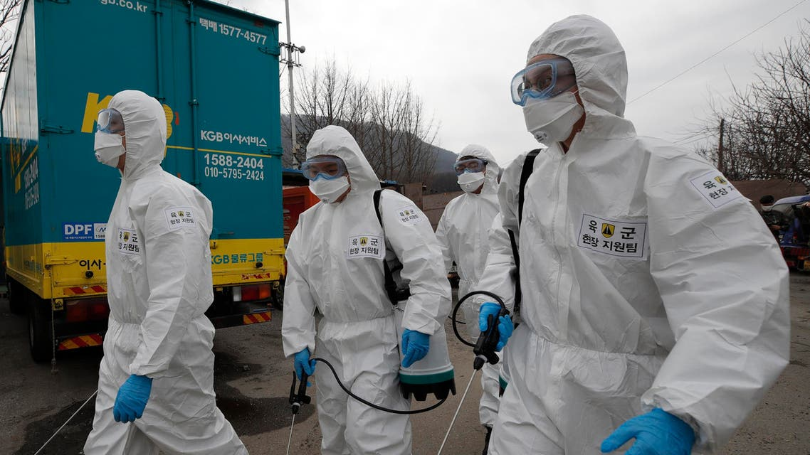 South Korean soldiers wearing protective gears walk to spray disinfectant as a precaution against the coronavirus in Seoul, South Korea on March 3, 2020. (AP)