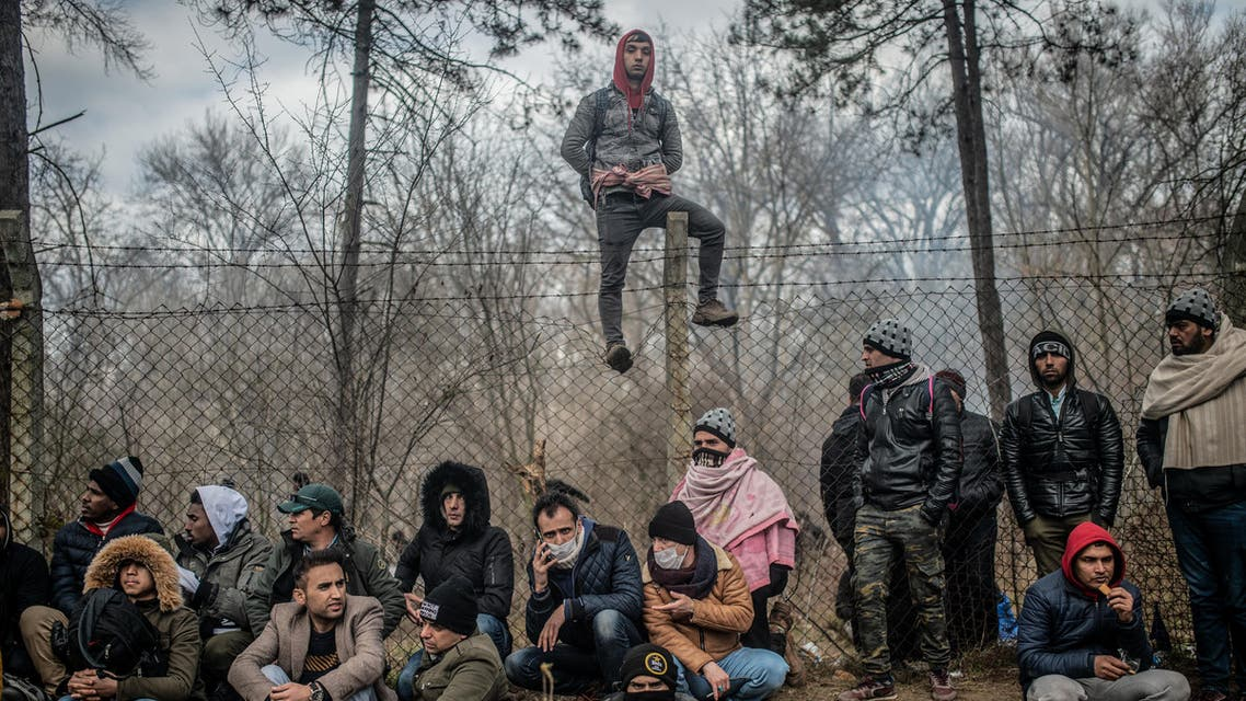 Migrants sit waiting near the buffer zone at Turkey-Greece border, at Pazarkule, in Edirne district. (AFP)