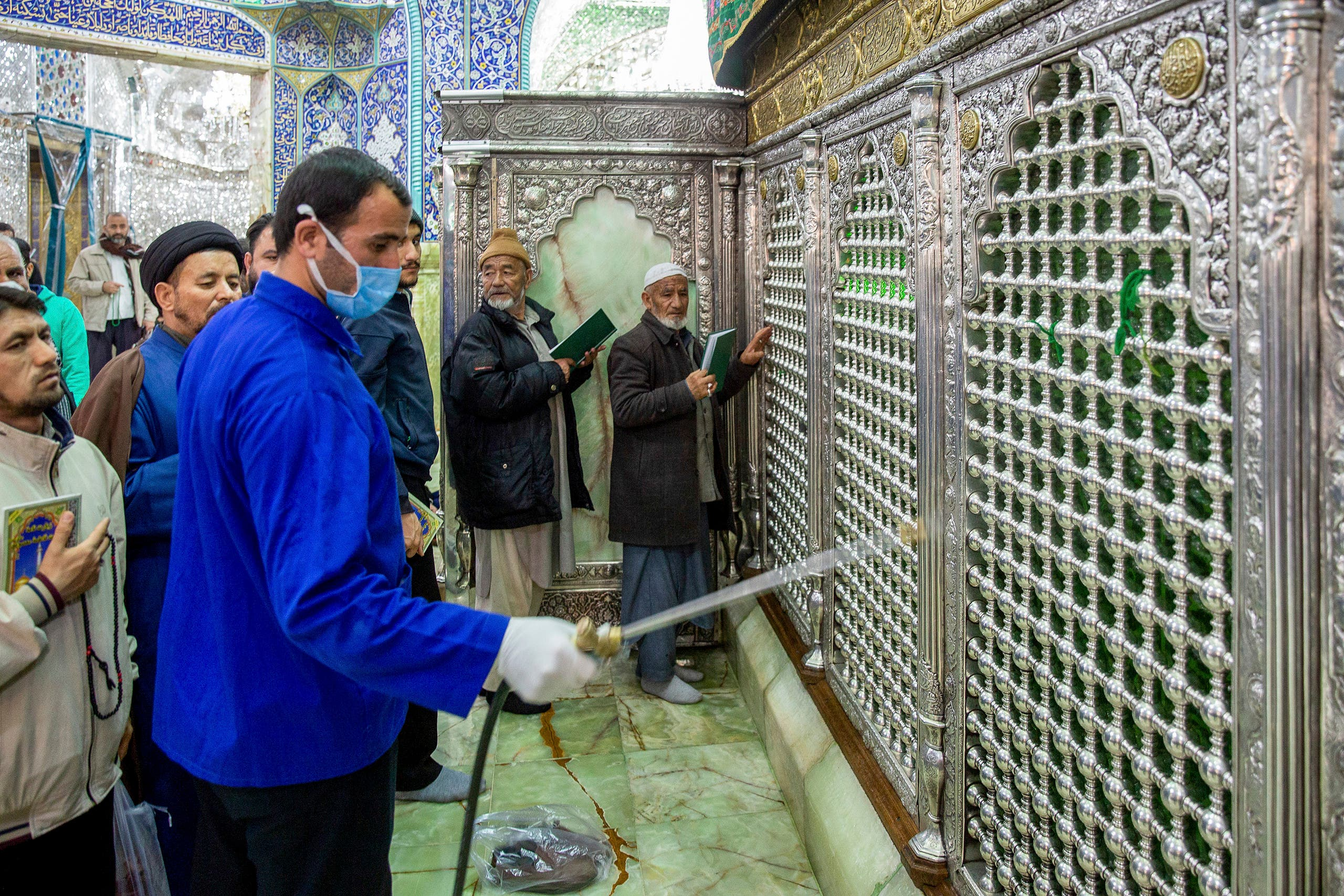 A a man disinfects the shrine of Saint Masoumeh against coronavirus in the city of Qom, Iran. (AP)