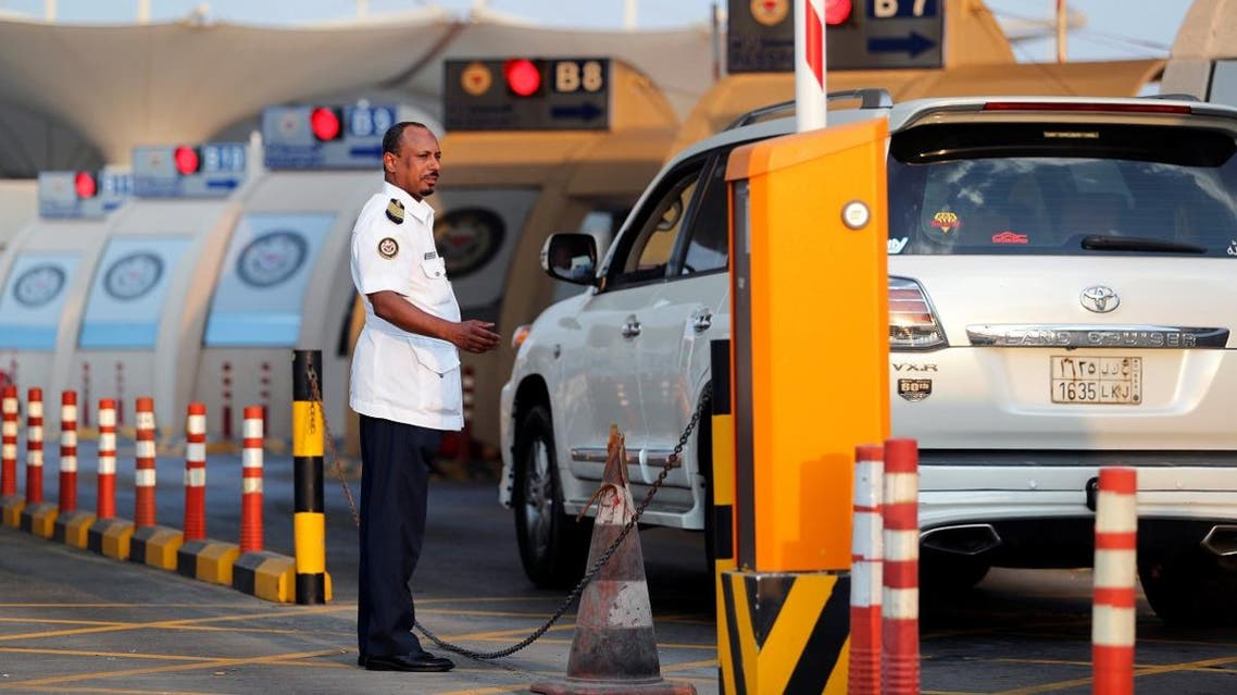 An Immigration officer assists cars arriving during rush hour at the Bahrain Immigration check point at King Fahd Causeway. (Reuters)