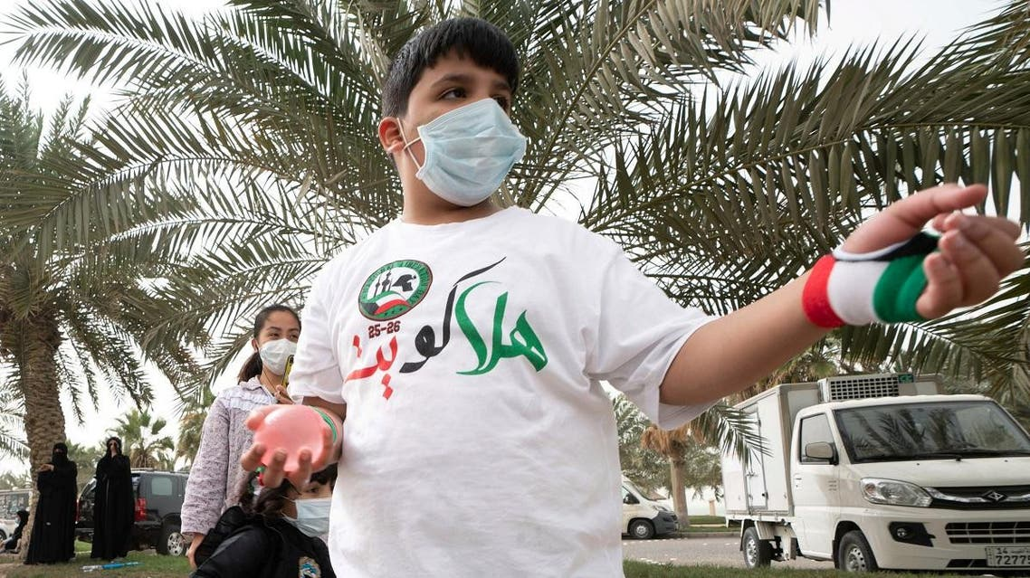 A Kuwaiti boy wears a protective face mask, following the outbreak of the new coronavirus, as he throws water at passing cars, during celebrations for the 29th Kuwait Liberation Day from the Iraqi occupation, in Kuwait City, February 26, 2020. (Reuters)