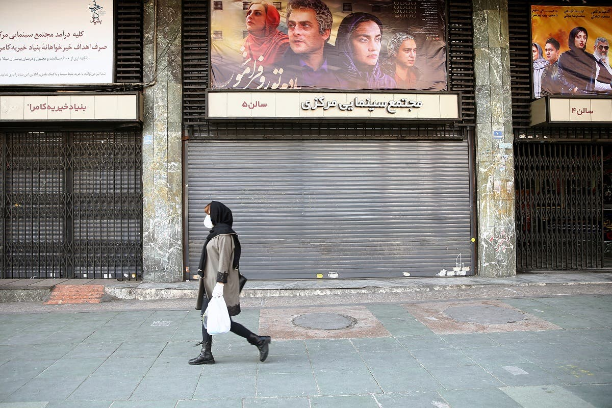An Iranian woman wears a protective mask to prevent contracting coronavirus, as she walks on a street in front of a closed cinema in Tehran. (Reuters)