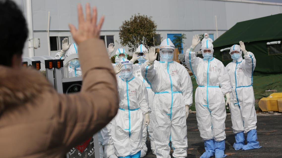 Medical personnel in protective suits wave hands to a patient who is discharged from the Leishenshan Hospital after recovering from the coronavirus, in Wuhan, in Hubei province, China, March 1, 2020. (Reuters)