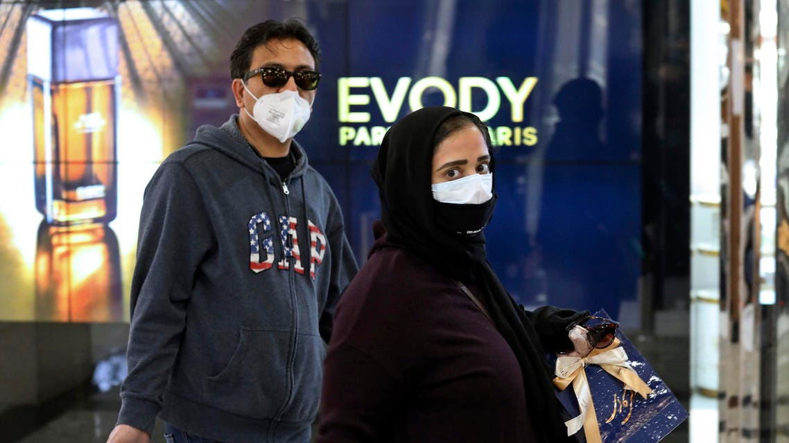 People wearing face masks shop in northern Tehran on March 3, 2020. (AP)